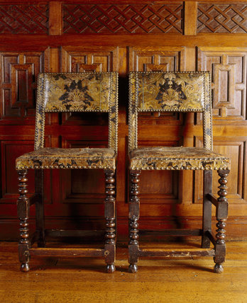 Close view of two embossed Spanish leather chairs against the wood panelling in the Inner Hall at Dunster Castle