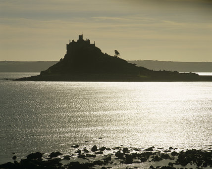 St. Michael's Mount on its tidal island silhouetted against the sky. The sunlight is reflected of the surface of the sea water making it look silver.
