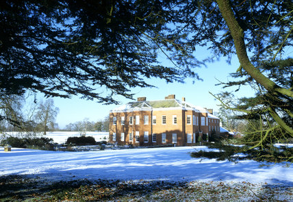 A view of the House at Hatchlands, framed by evergreen trees, with a blanket of snow over the ground