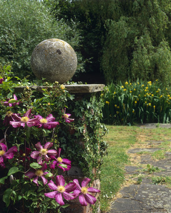 Stone sphere on a pedestal in the garden at St. John's Jerusalem in June. Pink flowers bloom in the foreground.