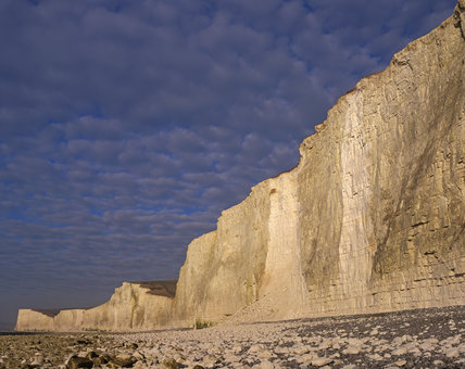 The Seven Sisters in the region of the Birling Gap, with a boulder strewn shore in the foreground