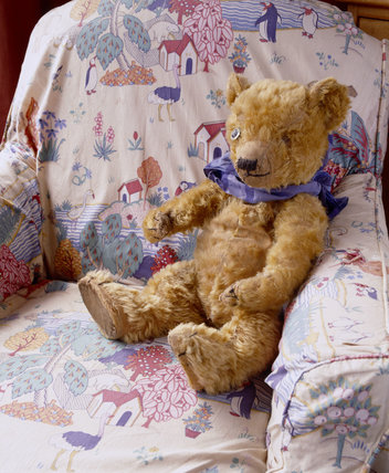 Lord Wraxall's Teddy Bear sitting on a chair covered with a nursery print in the Day Nursery at Tyntesfield