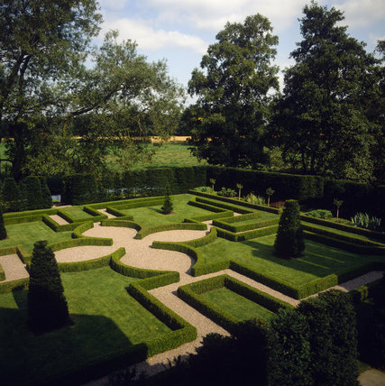 Little Moreton, view of The Knot Garden in summer with low green hedges enclosing areas of grass