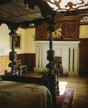 The Knights' Bedroom at Lyme Park, with a partial view of the four poster bed and looking toward the fireplace and the elaborately carved overmantel