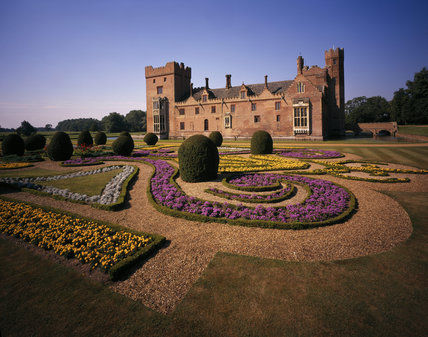 The east front of Oxburgh Hall seen across the Parterre, the geometric beds, of which, are planted with colourful flowers