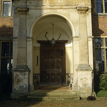 The imposing Entrance Portico in the east front, with heavy wooden door, bell pull, benches and stag's head