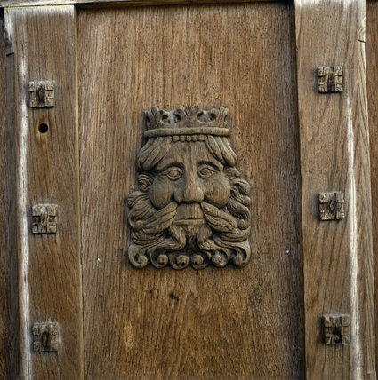 Detail of a carved head of a crowned and bearded man, on the door of the main entrance in the east front
