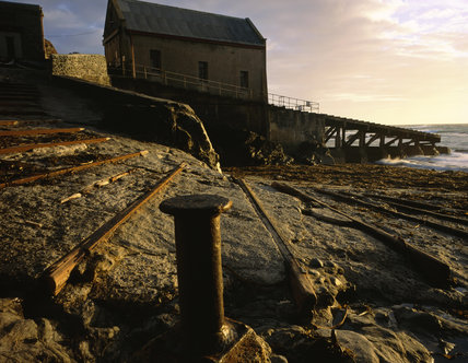 The derelict lifeboat station at Polpeor Cove on the Lizard Peninsula with the remains of the earlier slipway in the foreground