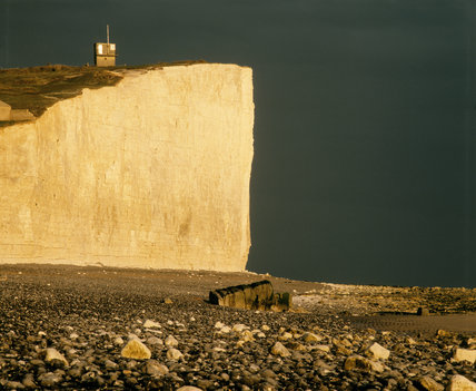 Dramatic white face of cliff silhouetted against the dark sea, at Birling Gap, East Sussex