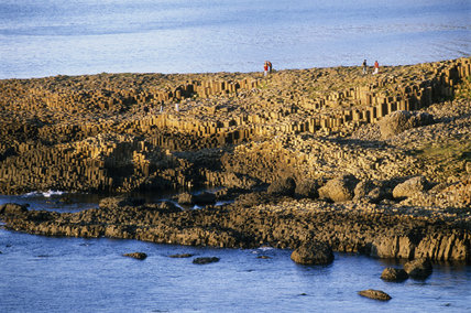 People stand on the rock formations amongst the coastline at Giant's Causeway