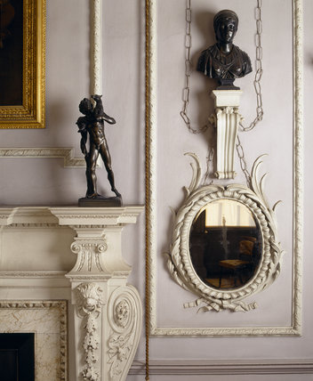A close up view in the Dining Room at Felbrigg Hall, showing a detail of the stucco fireplace, a bronze bust and statuette and an oval mirror