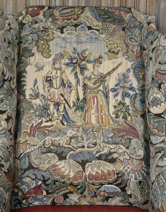 Close-up view of the back of an armchair bearing a detailed embroidery of a man and lady surrounded by many creatures
