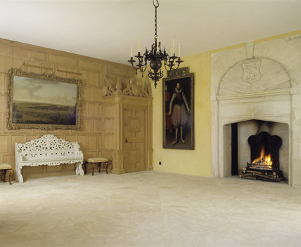 View of large entrance hall showing one of the internal wooden porches, fireplace & arch with its chevron overmantel decoration in which Emily Sherborne inserted a shield with her monogram