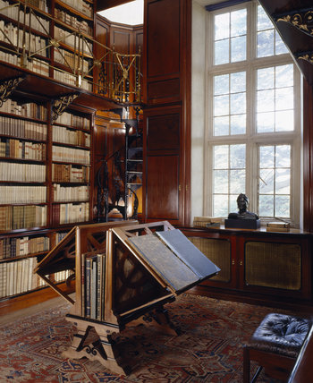 A corner of the Dante Library showing the spiral staircase to the second tier, the large double sided lectern and the bust of Dante, by Sabatino de Angelis (b. 1838)