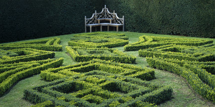 View of Knot Garden in the grounds of Antony House with corner bench in front of surrounding box hedge