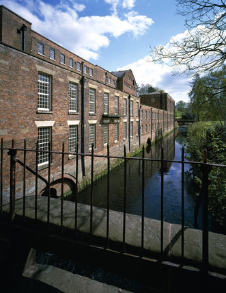 Rear view of Quarry Bank Mill by the side of the River Bollin
