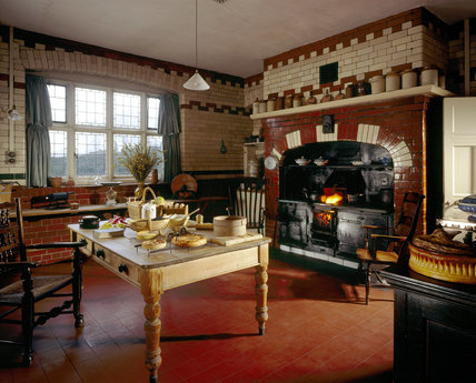The Kitchen at Wightwick Manor, looking towards the table with cooking implements and ingredients and the range with fire lit