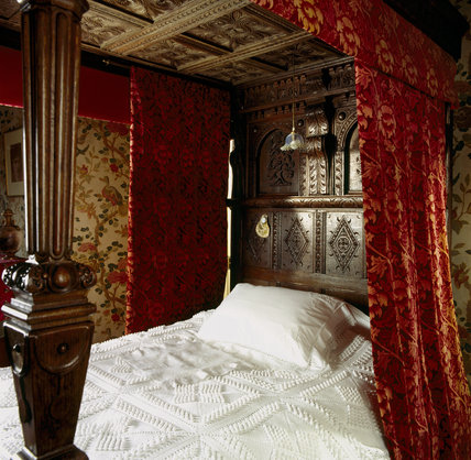 The bed in the Indian Bird Bedroom at Wightwick Manor; the bedstead is made out of pieces of Jacobean carving and the