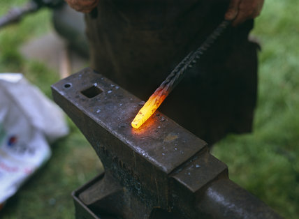 Close view of a white hot metal rod on a blacksmith's anvil at the Countryside and Craft Fair at Morden Hall Park in the London suburb of Merton