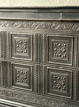 Close view of 18th century wood panelling at Llanerchaeron showing the detail of a carved frieze with formalised foliage above and below and four panels with formal centre pieces
