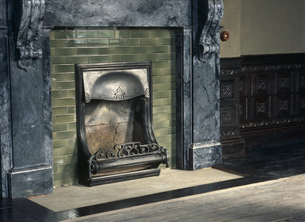 Close view of Victorian iron fireplace and grate at Llaner- chaeron with details of wrought iron decoration, glazed bricks and heavy carved slate corbels