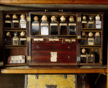 Close view of the medicine cabinet at Dunster Castle showing jars containing