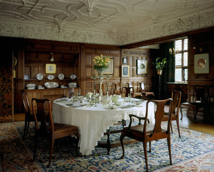 View of the Dining Room at Wightwick Manor with table in the centre set for dinner looking towards built-in sideboard and bay window