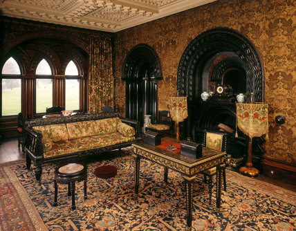 View of The Ebony Room at Penrhyn Castle including the fireplace, desk, carved wooden stool and sofa