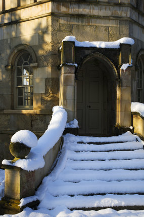 Steps and door to the Octagon Tower under snow on the valley side at Studley Royal Water Gardens, North Yorkshire