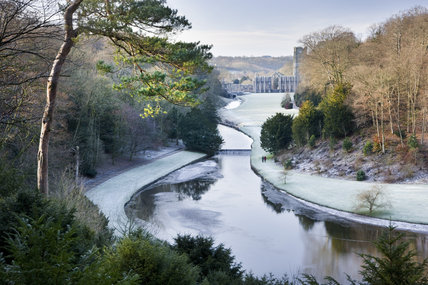 Looking over the Half Moon Pond and weir of Studley Royal Water Garden in winter from the Surprise View towards Fountains Abbey, North Yorkshire