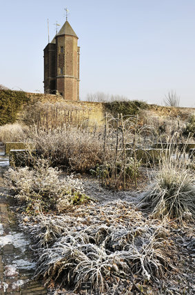The Elizabethan tower surrounded by the frosty January plants at Sissinghurst Castle Garden, near Cranbrook, Kent