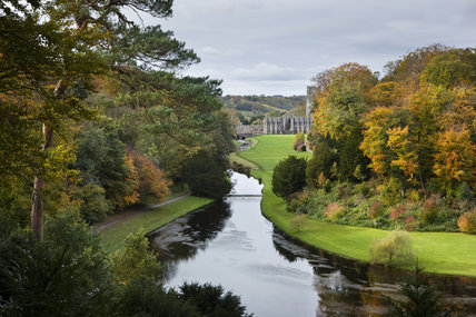 Looking over the Half Moon Pond and weir of Studley Royal Water Garden from the Surprise View towards Fountains Abbey, North Yorkshire