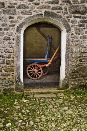Old farm cart glimpsed through an arch in an outbuilding on the estate at Godolphin House, near Helston, Cornwall