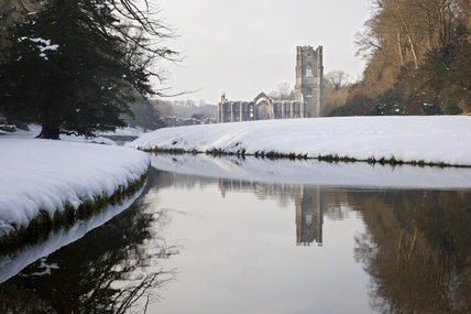 A view along the River Skell in winter towards Fountains Abbey, North Yorkshire, a Cistercian community of monks from the twelfth century until the Dissolution in 1539