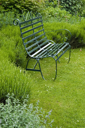 Ornamental garden seat against the herbaceous border in the garden at Oxburgh Hall, Norfolk, a fifteenth century moated manor house, home to the Bedingfeld family since 1482
