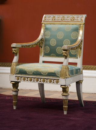 One of the Picture Gallery armchairs replaced in position after the new red carpet has been fitted at Attingham Park, Shropshire