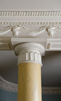 Close view of the frieze and part of the Doric columns in the Entrance Hall at Newark Park, Gloucestershire