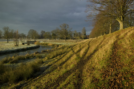 A view over the River Dene with the tracks on the bank made by deer, in the deer park at Charlecote Park, Warwickshire