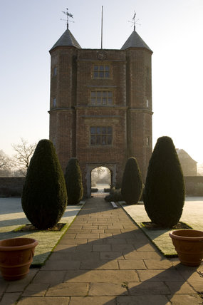 The Elizabethan Tower and topiary on the Upper Lawn at sunrise in winter at Sissinghurst Castle Garden, near Cranbrook, Kent