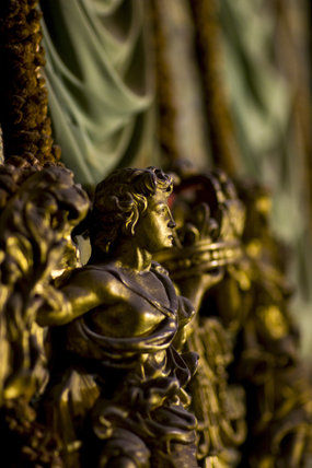 Detail of gilded figure on the headboard of the King James II bed prior to conservation and cleaning at Knole, Kent