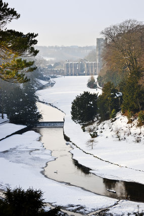 A beautiful view looking over the Half Moon Pond and weir of Studley Royal Water Garden in winter, from the Surprise View towards Fountains Abbey, North Yorkshire
