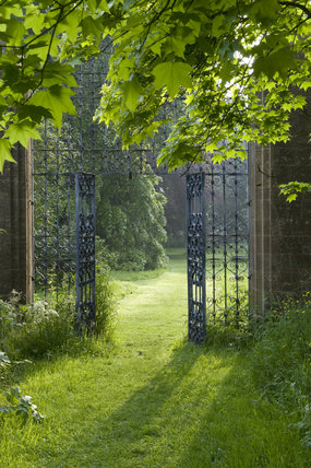 An early morning view of the ornamental wrought iron gate to the East Orchard at Barrington Court, Somerset