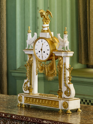 Regency gilt clock on a side table in the Drawing Room at Castle Drogo, Devon