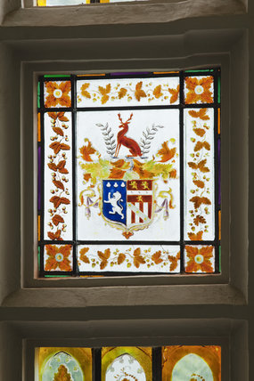 The central panel of the bay window on the Staircase which contains the armorial bearings of Lewis Clutterbuck at Newark Park, Gloucestershire