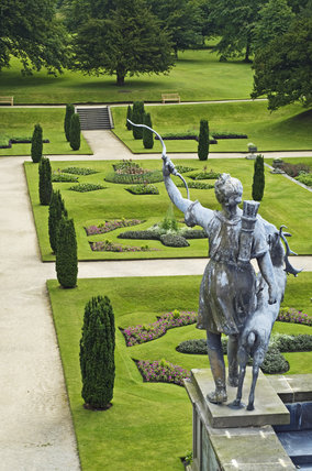 Statue of Diana overlooking the Orangery Terrace with clipped irish yew trees and intricately patterned beds at Lyme Park, Cheshire