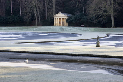 A winter view of the Temple of Piety seen over the Canal and Half-Moon pond, at Studley Royal Water Garden, North Yorkshire