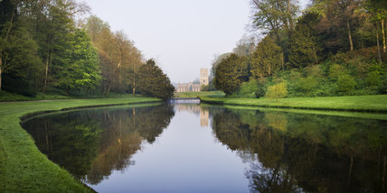 A view over the Half Moon Pond and weir of Studley Royal Water Garden towards Fountains Abbey, North Yorkshire