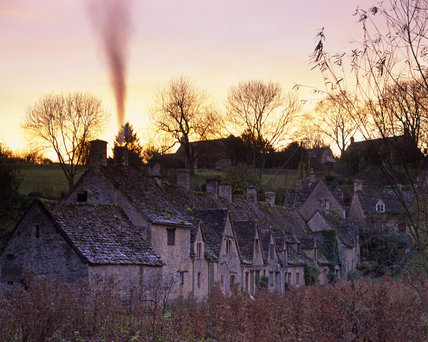Dusk falls at Arlington Row, Bibury, Gloucestershire - an ancient stone building which was converted to cottages in the seventeenth century