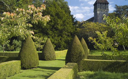 View to All Saints Church from The Orchard with its topiary and straight hedging at Hinton Ampner, Hampshire