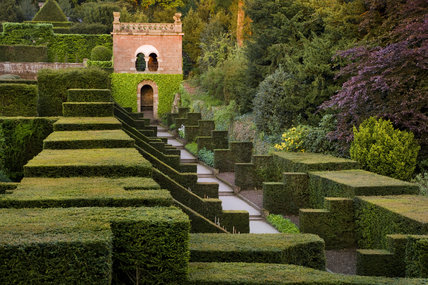 View over the compartmentalised hedging of the Dahlia Walk towards the Shelter House at Biddulph Grange Garden, Staffordshire